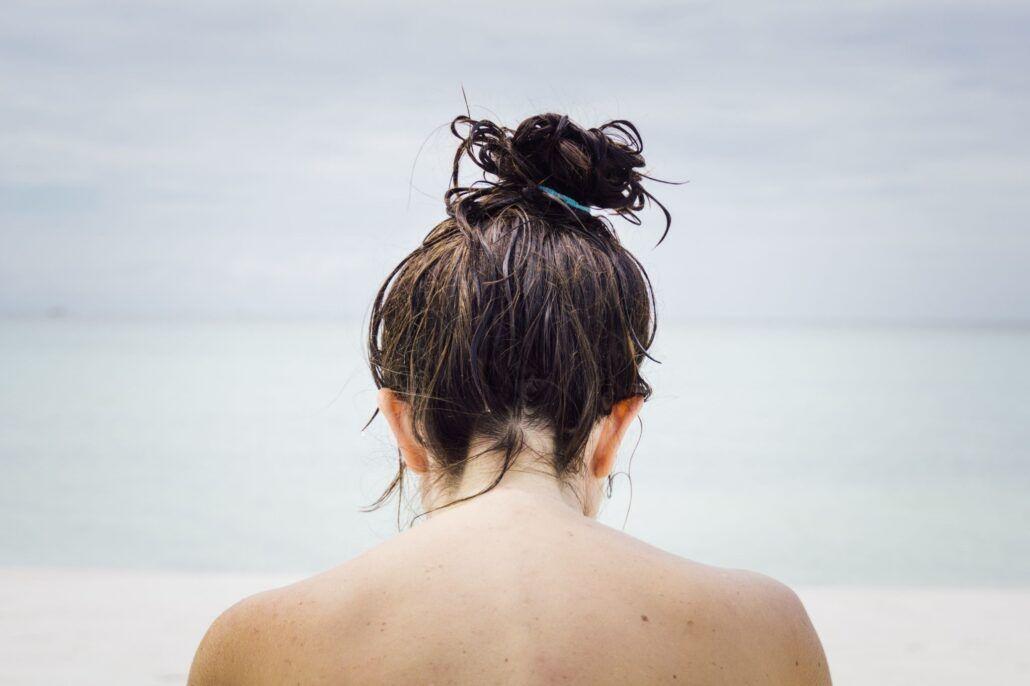 Zdravé vlasy - žena na pláži s vlasmi v cope