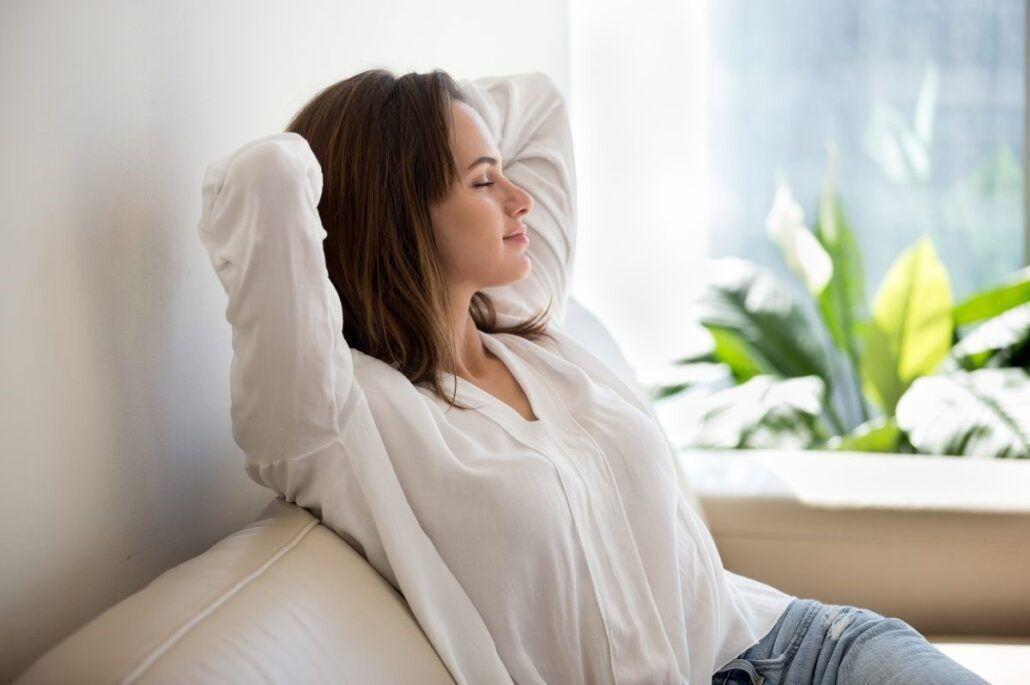 Mindfulness - žena so zatvorenými očami relaxuje na pohovke